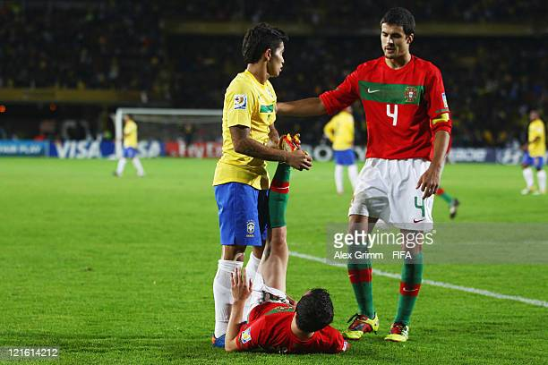 Mario Rui of Portugal receives treatment by Dudu of Brazil and team mate Nuno Reis during the FIFA U20 World Cup 2011 final between Brazil and...