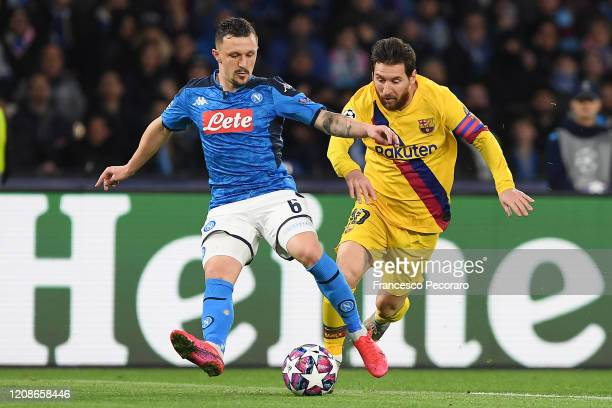 Mario Rui of SSC Napoli vies with Lionel Messi of FC Barcelona during the UEFA Champions League round of 16 first leg match between SSC Napoli and FC...