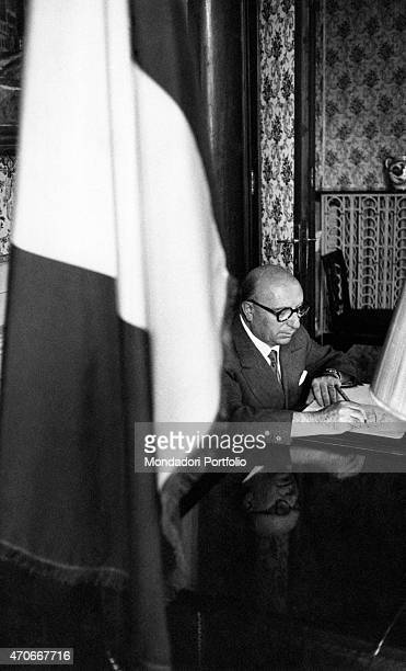 'MP Mario Scelba Home Affair Minister during Fanfani Cabinet sits at the writing desk of his study in Viminale in the closeup the Italian flag Rome...