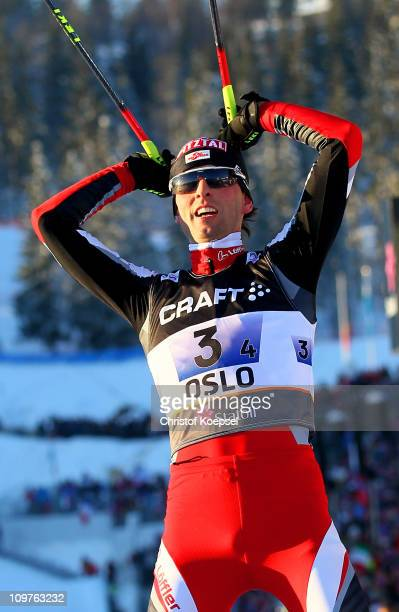 Mario Stecher of Austria celebrates winning the gold medal as he crosses the finish line in the Nordic Combined Team 4x5km race during the FIS Nordic...