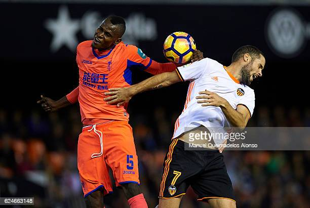 Mario Suarez of Valencia competes for the ball with Uche Henry-Agbo of Granada during the La Liga match between Valencia CF and Granada CF at...