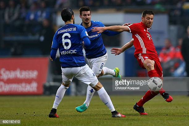 Mario Vrancic and Jerome Gondorf of Darmstadt challenge Xabi Alonso of Bayern Muenchen during the Bundesliga match between SV Darmstadt 98 and Bayern...