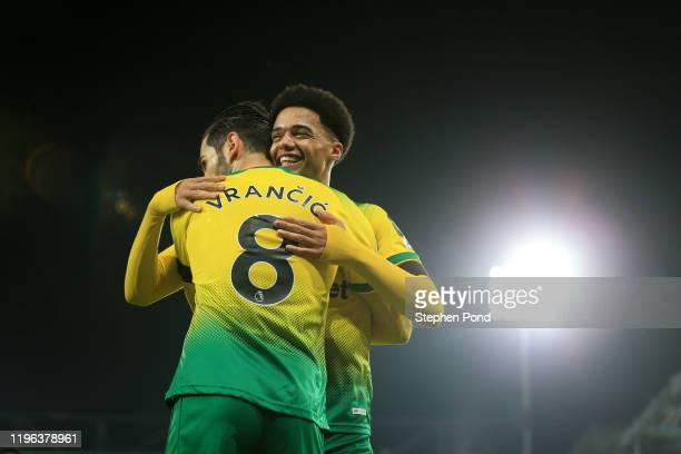 Mario Vrancic of Norwich City celebrates with teammate Jamal Lewis of Norwich City after scoring his team's first goal during the Premier League...