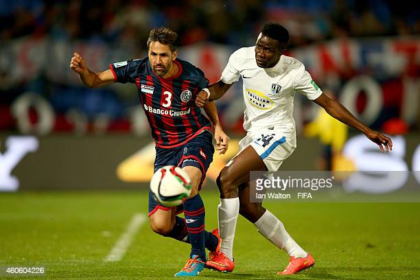 Mario Yepes of San Lorenzo is tackled by Sanni Issa of Auckland City FC during the FIFA Club World Cup Semi Final match between San Lorenzo v...