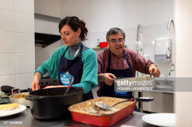 Marion and LouisMarie volunteers prepare a dinner at an 'Escale Solidaire' in the 6th district of Lyon centraleastern France on November 11 2018 The...