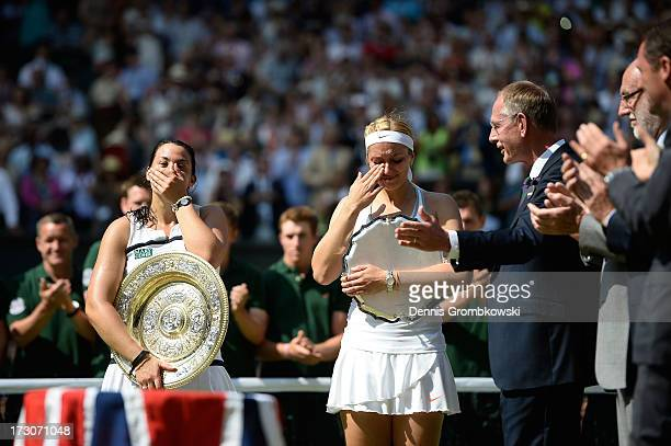 Marion Bartoli of France and Sabine Lisicki of Germany react as they hold their trophies following the presentation ceremony after their Ladies'...