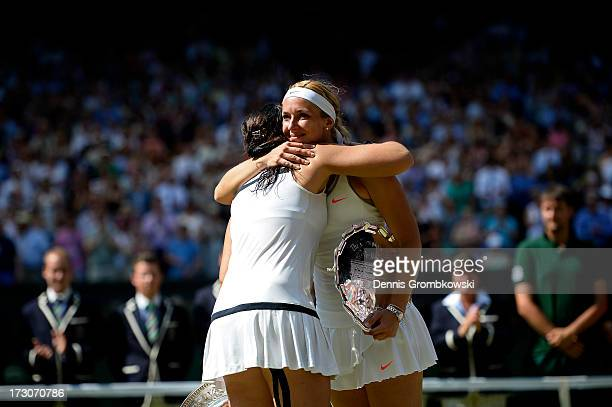 Marion Bartoli of France embraces Sabine Lisicki of Germany after the trophy presentation following their Ladies' Singles final match on day twelve...