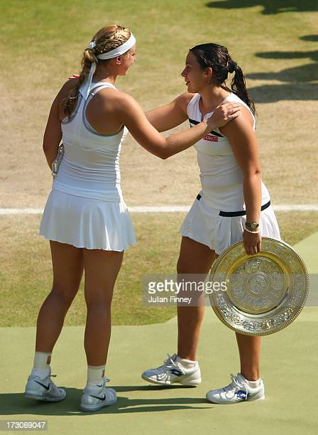 Marion Bartoli of France holds the Venus Rosewater Dish trophy as she speaks with Sabine Lisicki of Germany following the trophy presentation after...