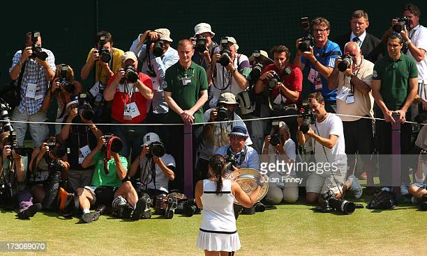Marion Bartoli of France poses with the Venus Rosewater Dish trophy in front of photographers after her victory in the Ladies' Singles final match...