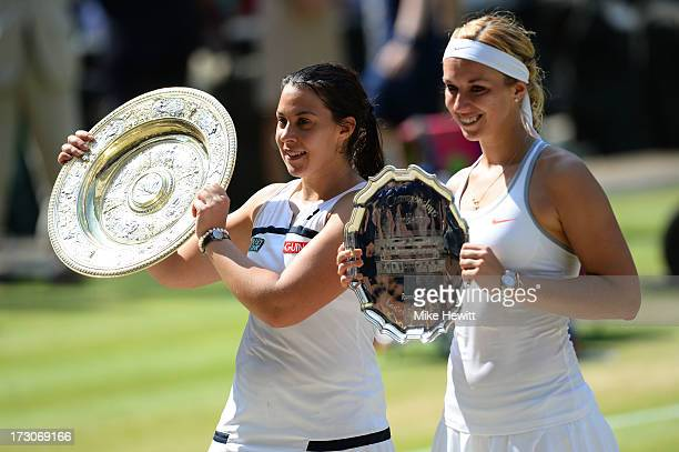 Marion Bartoli of France poses with the Venus Rosewater Dish trophy next to Sabine Lisicki of Germany and her runnerup trophy after their Ladies'...