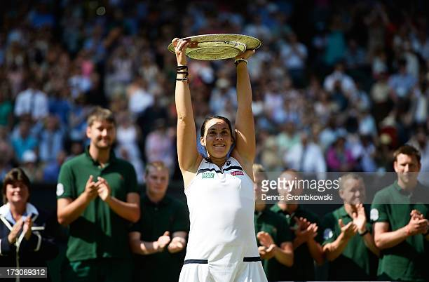 Marion Bartoli of France poses with the Venus Rosewater Dish trophy after her victory in the Ladies' Singles final match against Sabine Lisicki of...