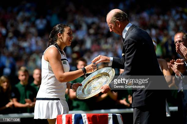 Marion Bartoli of France receives the Venus Rosewater Dish trophy from Prince Edward Duke of Kent after her victory in the Ladies' Singles final...