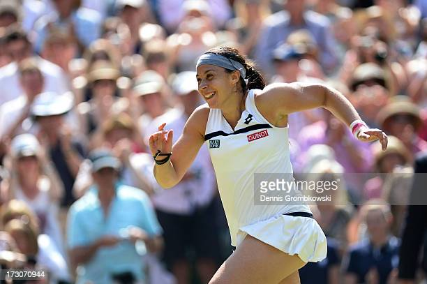 Marion Bartoli of France runs to her box as she celebrates victory after the Ladies' Singles final match against Sabine Lisicki of Germany on day...