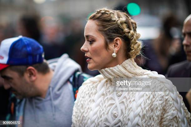 Marion Cotillard wears a white turtleneck wool pull over has a braid hairstyle outside Jean Paul Gaultier during Paris Fashion Week Haute Couture...