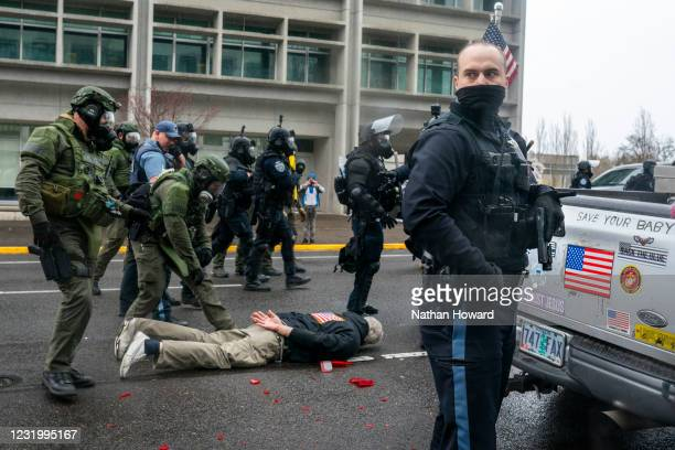Marion Counter Sheriff's deputies and Oregon State Troopers arrest a driver who pulled a handgun on protesters after they broke his trucks lights on...