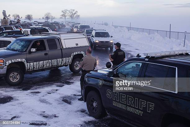 TOPSHOT Marion County Sheriff deputies help park vehicles at the Harney County Fairgrounds ahead of a meeting in Burns Oregon on January 6 2016 The...