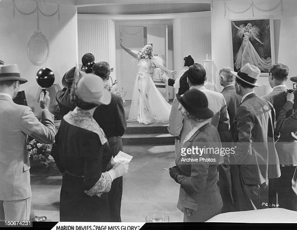 Marion Davies striking a pose for Mary Astor and others in a scene from the film 'Page Miss Glory' 1935