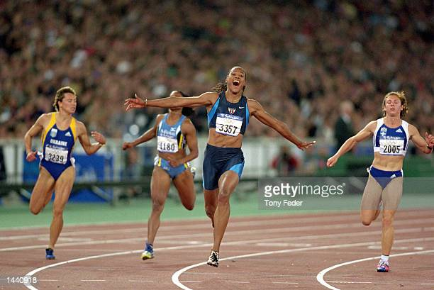 Marion Jones of the USA reacts emotionally after crossing the finish line to win the gold medal in the women's 100m final at the Olympic Stadium...