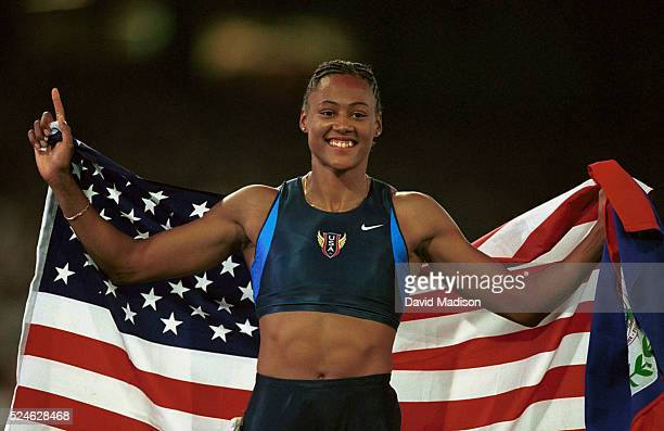 Marion Jones smiles and holds the Stars and Stripes after winning gold in the women's 200m final during the Sydney 2000 Olympics
