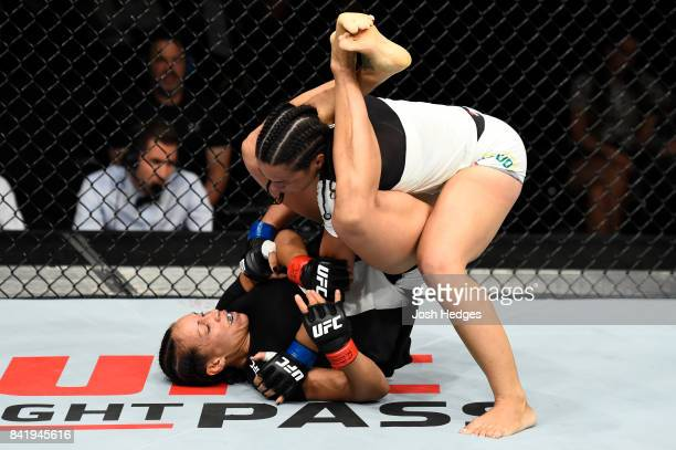 Marion Reneau attempts to armbar Talita Bernardo of Brazil in their women's bantamweight bout during the UFC Fight Night event at the Rotterdam Ahoy...