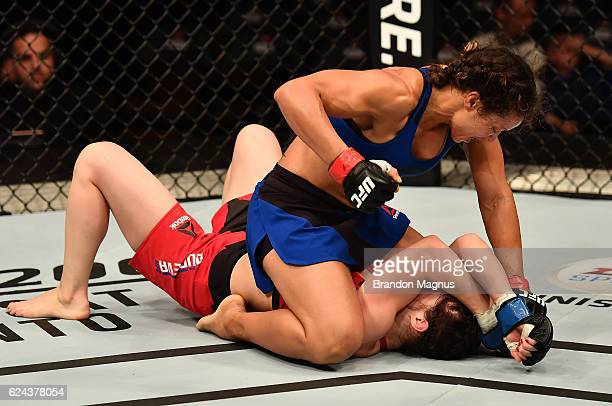 Marion Reneau punches down at Milana Dudieva of Russia in their women's bantamweight bout during the UFC Fight Night at the SSE Arena on November 19...
