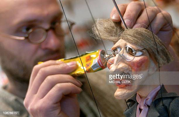 A marionettes maker sticks glasses on the head of a puppet in a store near Charles Bridge in Prague 'Little Side' district 11 December 2006 Czech...