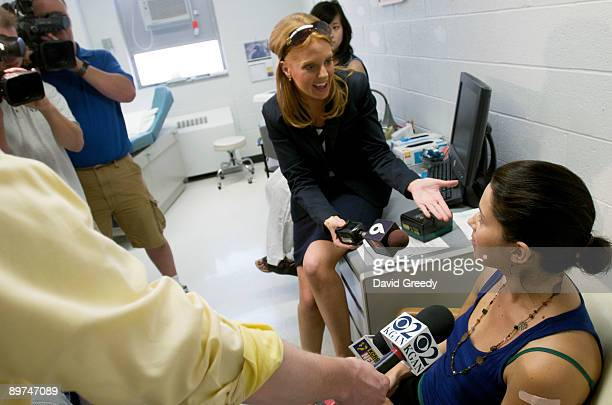 Marisa Grunder, 27 of Wilton, Iowa, speaks to the media after receiving an H1N1 vaccine, developed by CSL of Australia, during clinical trials at...