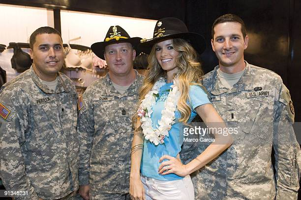 Marisa Miller poses with US Army soldiers SPC Ricardo Perilla SGM Edward Dunn and Lt Joseph Lewandowski at the grand opening of Hawaii's first ever...