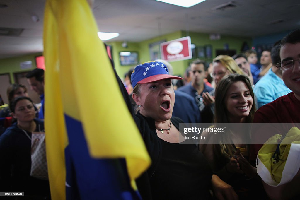 Marisa Perez holds a Venezuelan flag as she reacts to what is being said on a television set reporting on the death of Venezuelan president Hugo Chavez, at El Arepazo 2 a restaurant in the heart of a neighborhood that has the largest concentration of Venezuelans in the U.S. on March 5, 2013 in Doral, Florida. The Venezuelan government announced today that Hugo Chavez lost his battle with cancer.