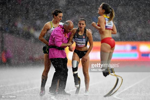 Marissa Papaconstantinou of Canada is helped from the track by Irmgard Bensusan of Germany after competing in the Womens 200m T44 final during day...