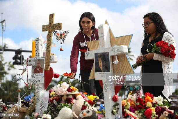Marissa Rodriguez and Ambar Ramirez visit a makeshift memorial setup in front of Marjory Stoneman Douglas High School in memory of the 17 people that...