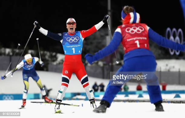 Marit Bjoergen of Norway celebrates as she crosses the finish line to win gold with Ingvild Flugstad Oestberg of Norway during the Ladies' 4x5km...