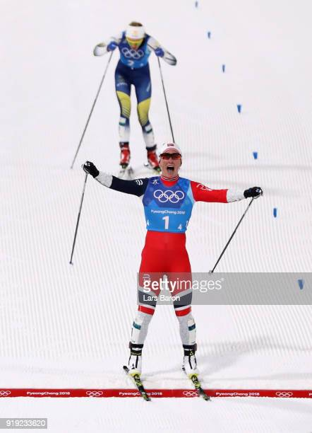 Marit Bjoergen of Norway celebrates as she crosses the finish line to win gold ahead of Stina Nilsson of Sweden during the Ladies' 4x5km Relay on day...
