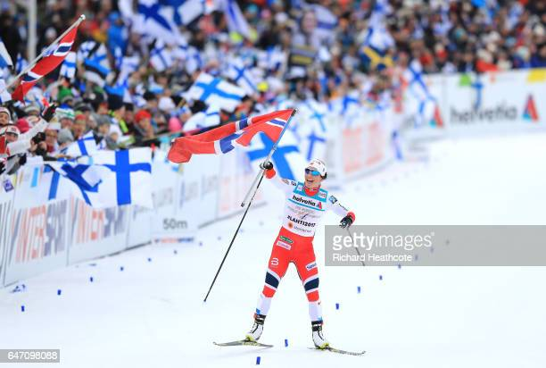 Marit Bjoergen of Norway celebrates as she races to the line to win gold during the Women's Cross Country 4x5km Relay at the FIS Nordic World Ski...