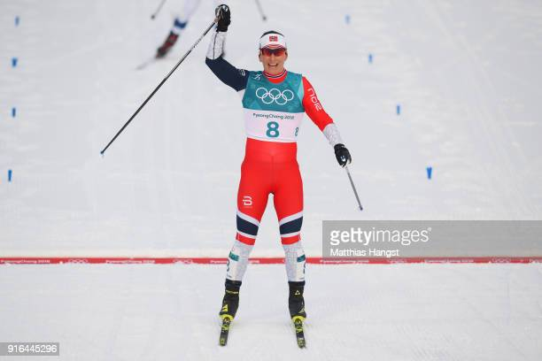 Marit Bjoergen of Norway celebrates crossing the finish line to win silver during the Ladies Cross Country Skiing 7.5km + 7.5km Skiathlon on day one...