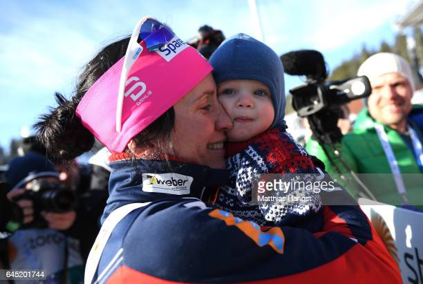 Marit Bjoergen of Norway celebrates her gold medal with her child after the Women's Cross Country Skiathlon during the FIS Nordic World Ski...