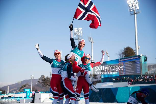 Marit Bjoergen of Norway celebrates her gold with team mates during womens 30k Mass Start Classic Technique at Alpensia CrossCountry Centre on...
