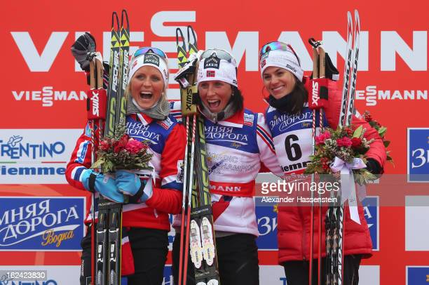 Marit Bjoergen of Norway celebrates victory on the podium with her Norwegian team-mates, second placed Therese Johaug and, third placed Heidi Weng ,...