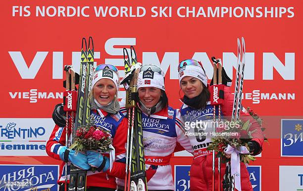 Marit Bjoergen of Norway celebrates victory on the podium with her Norwegian teammates second placed Therese Johaug and third placed Heidi Weng after...