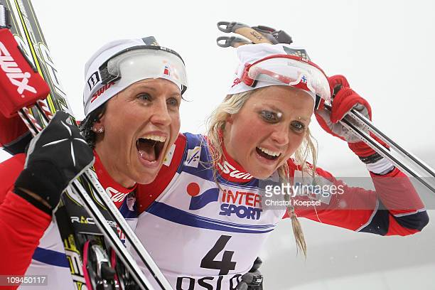Marit Bjoergen of Norway celebrates winning the gold medal with teammate and bronze medallist Therese Johaug of Norway following the Ladies Cross...