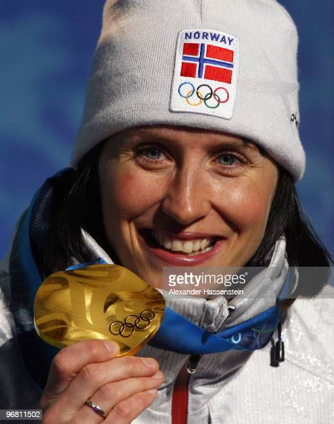 Marit Bjoergen of Norway celebrates with her gold medal during the medal ceremony for the Ladies' Individual Sprint CrossCountry on day 6 of the...