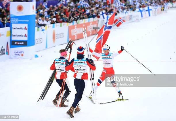 Marit Bjoergen of Norway celebrates with team mates as she crosses the line to win gold during the Women's Cross Country 4x5km Relay at the FIS...
