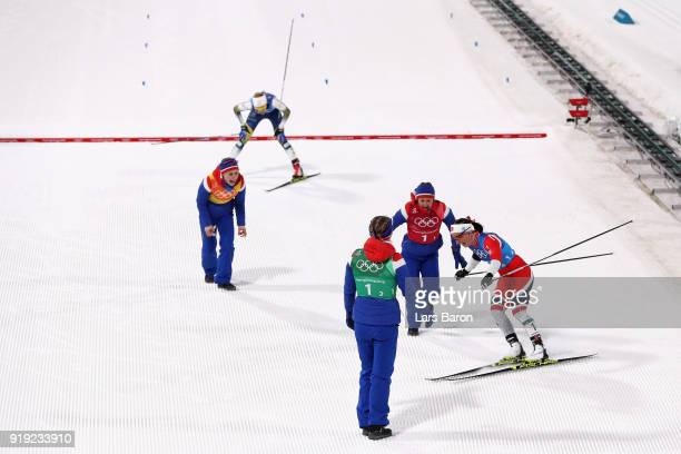 Marit Bjoergen of Norway celebrates with team mates as she crosses the finish line to win gold ahead of Stina Nilsson of Sweden during the Ladies'...