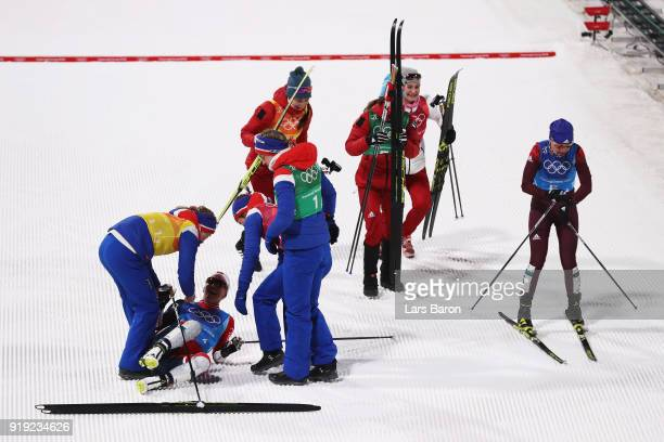 Marit Bjoergen of Norway celebrates with team mates as she crosses the finish line to win gold during the Ladies' 4x5km Relay on day eight of the...