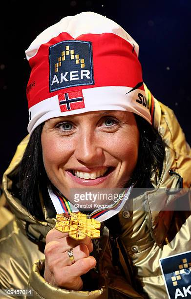 Marit Bjoergen of Norway celebrates with the the gold medal won in the Ladies Cross Country 15km Pursuit race during the FIS Nordic World Ski...