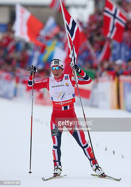 Marit Bjoergen of Norway crosses the line to claim victory in the Cross Country Women's Relay at the FIS Nordic World Ski Championships on February...