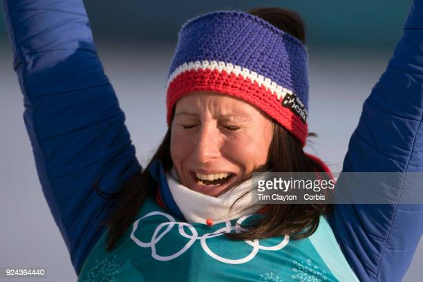 Marit Bjoergen of Norway in tears as she is presented as the gold medal winner of the CrossCountry Skiing Ladies' 30km Mass Start Classic during...