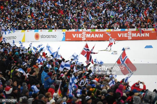 Marit Bjoergen of Norway is cheered on by spectators as she races to the line to win gold during the Women's Cross Country 4x5km Relay at the FIS...