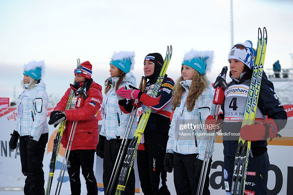 Marit Bjoergen of Norway, Justyna Kowalczyk of Poland and Charlotte Kalla of Sweden (L-R) wait for the flower ceremony after the women 10km free handicap start during the FIS World Cup Cross Country Skiing on November 28, 2010, in Kuusamo, Finland.