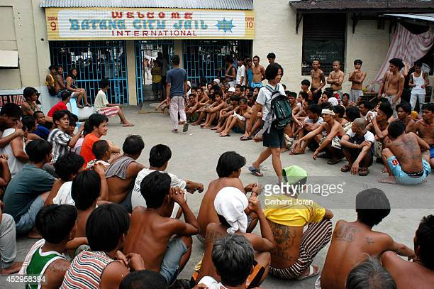 Marites Biado walks past gang members from BCJ during one of the 4 daily countings. The BCJ is one of 4 major gangs in Manila City Jail. Marites...
